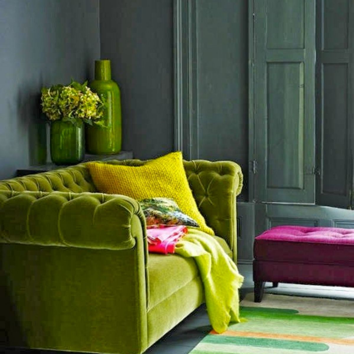 Velvet green sofa with dark grey walls and shutters pink footstool