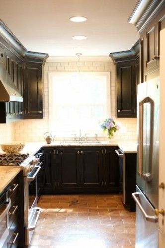 Small Kitchen With Warm Tile Floors In Brick Pattern Molding On Cabins Carrara White Marble Tops Large Stove Hood Ap