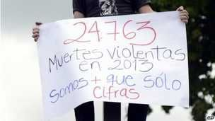 "A man holds a banner reading ""24,763 violent deaths in 2013 - we are more than just figures"""