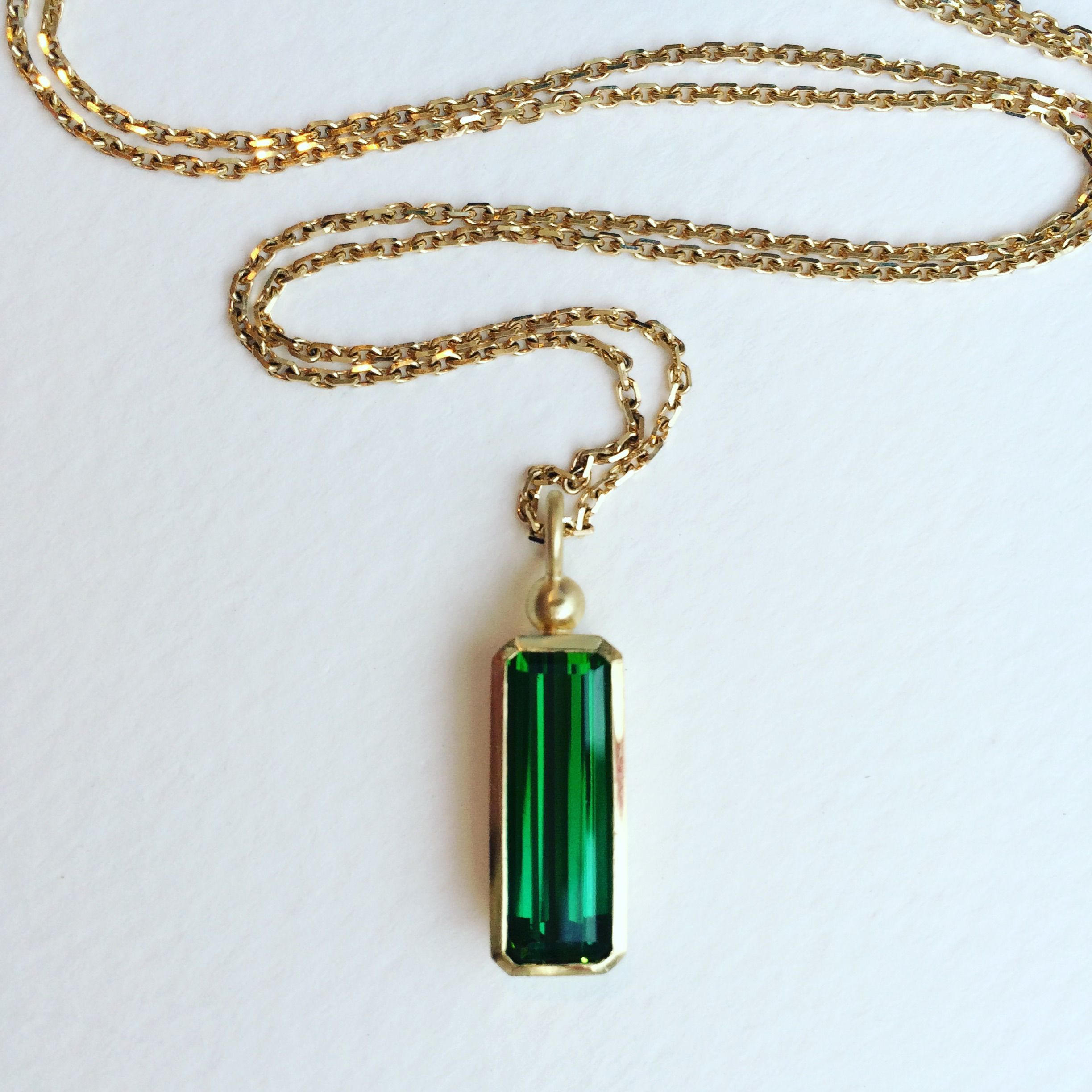 Deep green tourmaline pendant set in ct gold made by julia cook