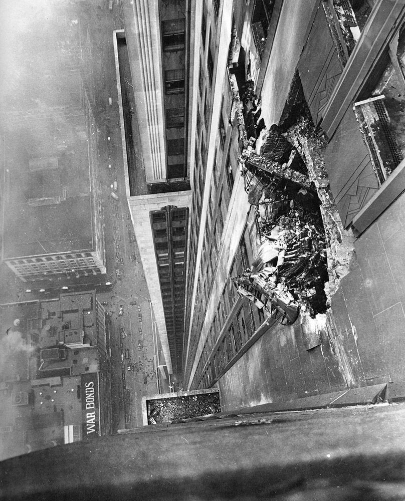 A B-25 Mitchell bomber crashed into the Empire State Building on the foggy morning of July 28, 1945. New York Times photographer Ernie Sisto had two of his friends hold his belt while he dangled off the side of the building to take this photograph of the remains of the plane still smashed into the outer wall.