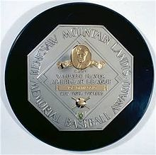 """A black circle with an octagonal silver plaque in the middle. The edge of the plaque reads """"KENESAW MOUNTAIN LANDIS MEMORIAL BASEBALL AWARD"""". In the middle of the octagon is a baseball diamond which contains, from the top, Judge Landis' face in gold, """"Most Valuable Player"""", the winner's league, his name in a gold rectangle, and his team."""