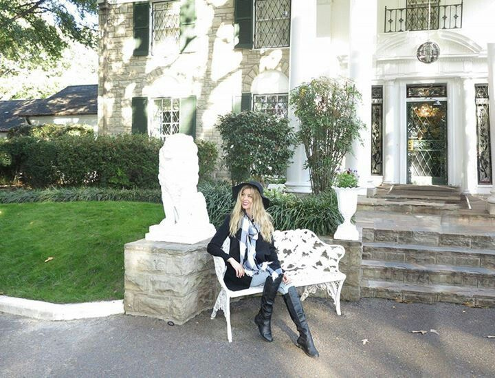 Sheridyn sitting in front of Elvis Presley's Graceland mansion.