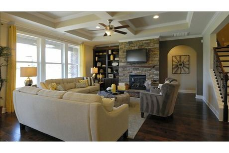 A stacked stone fireplace and coffered ceiling are just two of the
