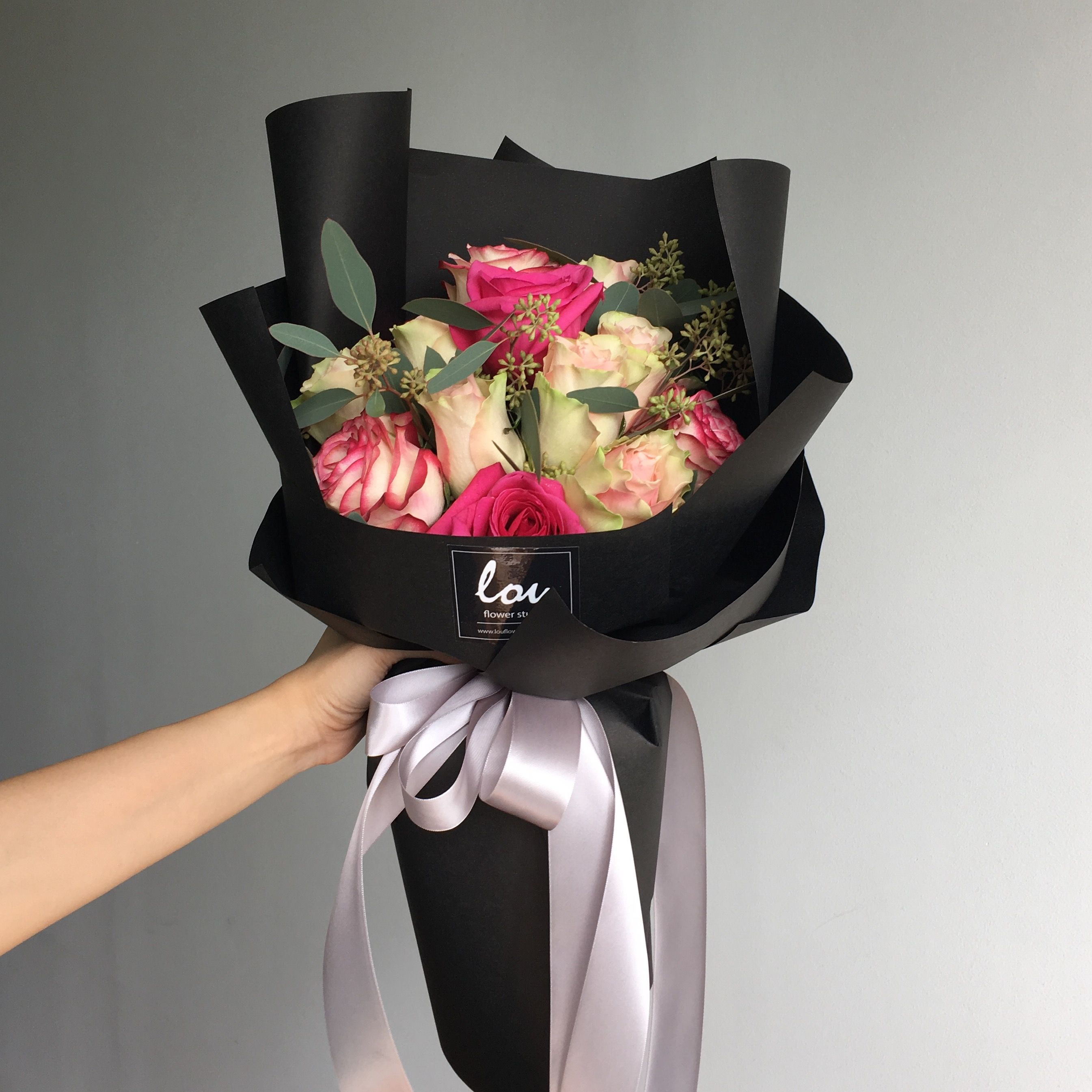 A Mix Of Ecuador Fuchsia Sylvie Matilda And Kenya Red Tipped Roses In Black Classic Wrap Bunga