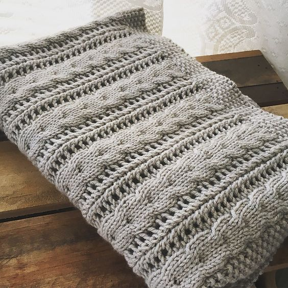 A cosy baby blanket with little cables and easy lace pattern. | Yarn ...