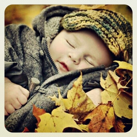 fall photo - cozy jacket, knitted cap, pile of leaves
