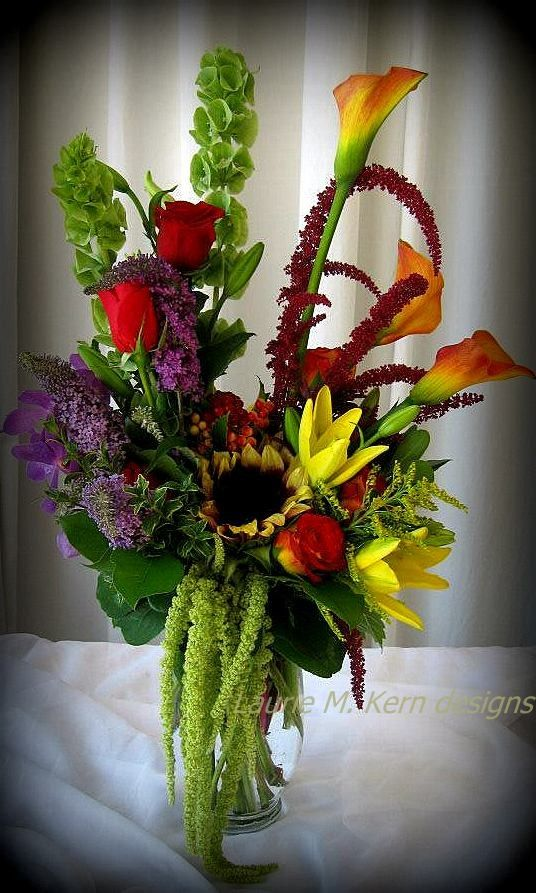 Sunflowers nestled under mango calla lilies, amaranths, butterfly bush, roses, bells of ireland, lily, solidago and more.  Artistic design makes this arrangement amazing and a one of a kind. $89.00