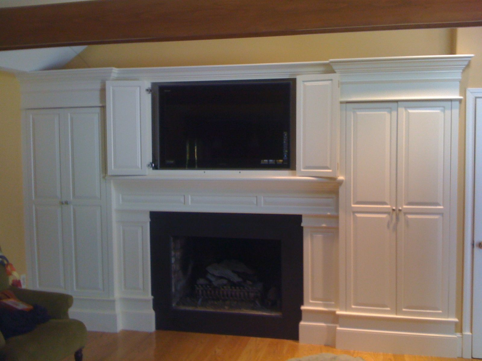 Fireplace surround with doors open to show LCD tv
