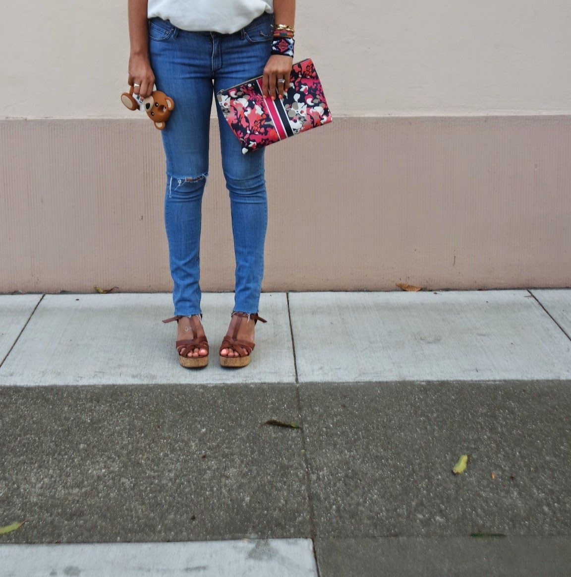 floral clutch, teddy bear phone case, ripped jeans