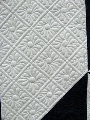 """This quilt won Viewer's Choice at the Oklahoma City Winter Quilt Show.  It was pieced by Elinor Rahm and is Marsha McCloskey's """"Triple Feathered Star"""" pattern.  Machine quilted by Amy Hunter.  These flowers are the background filler - BEAUTIFUL, aren't they?  Follow the link to find more close-ups."""