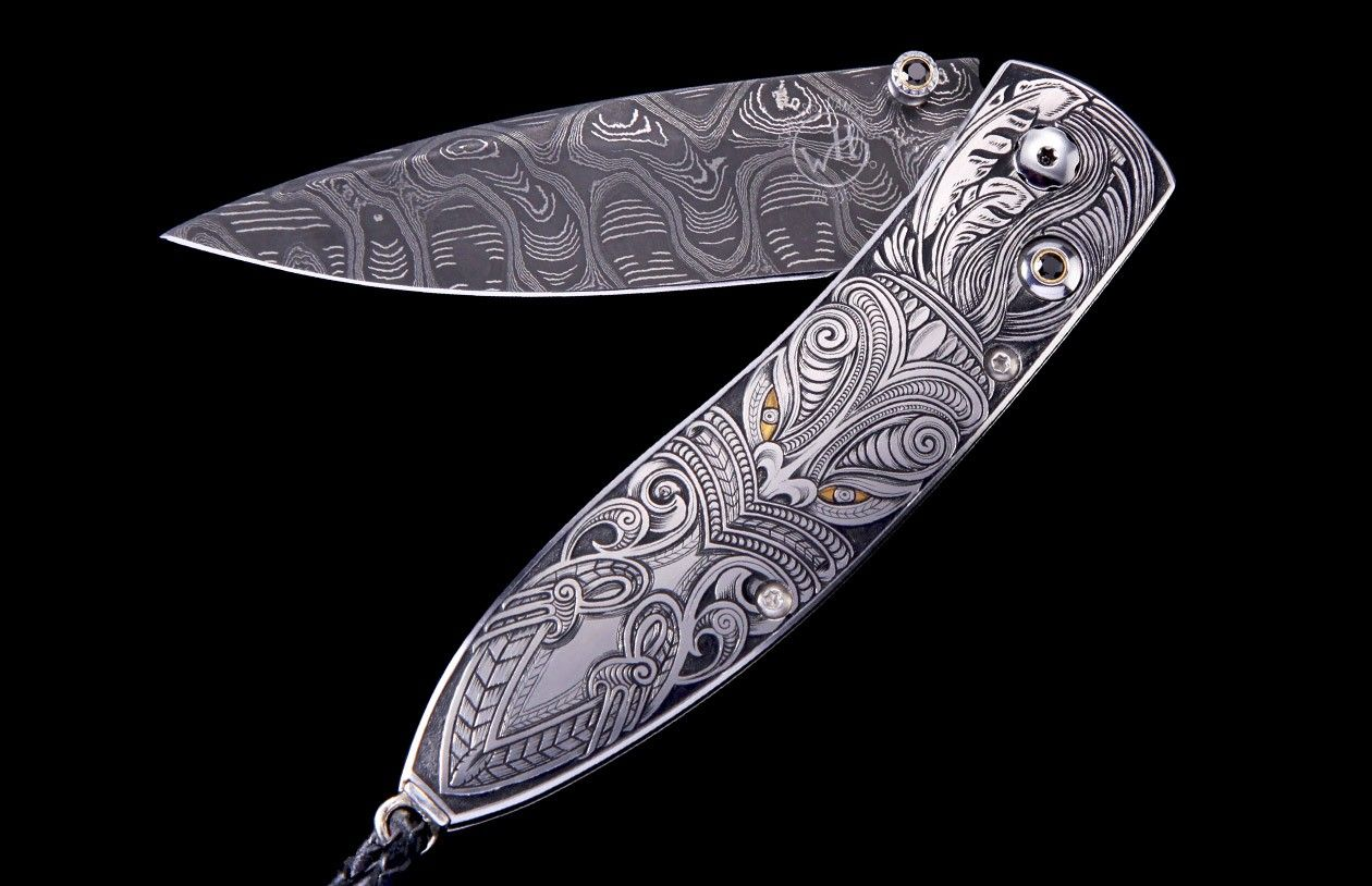 "William Henry's Monarch ""Taiaha"" features a mesmerizing handle finely hand-engraved with 24K gold inlays by Andrew Biggs. The blade is hand-forged Hornets Nest damascus by Mike Norris. The one-hand button lock and the thumb stud are set with spinel."