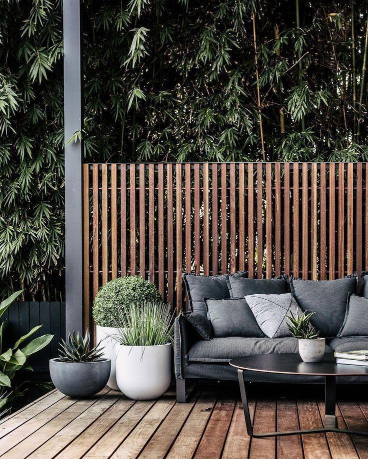 Photo of Moderner Sichtschutz aus Holzlastten, dazu dunkle Möbel und Pflanzen in großen…