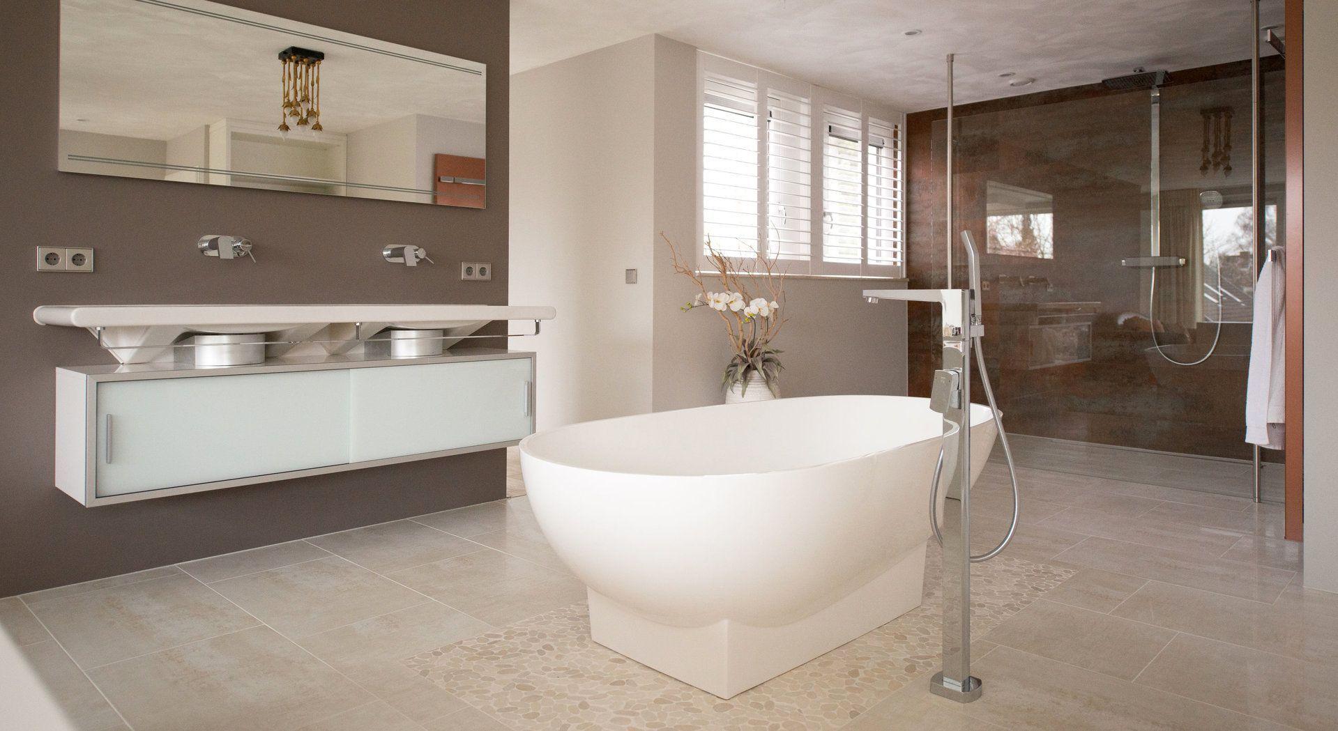 Royale badkamer met in het midden prominent het bad aanwezig ...