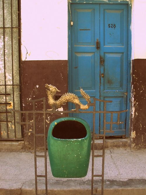 A beat-up blue door stands behind a golden dragon in