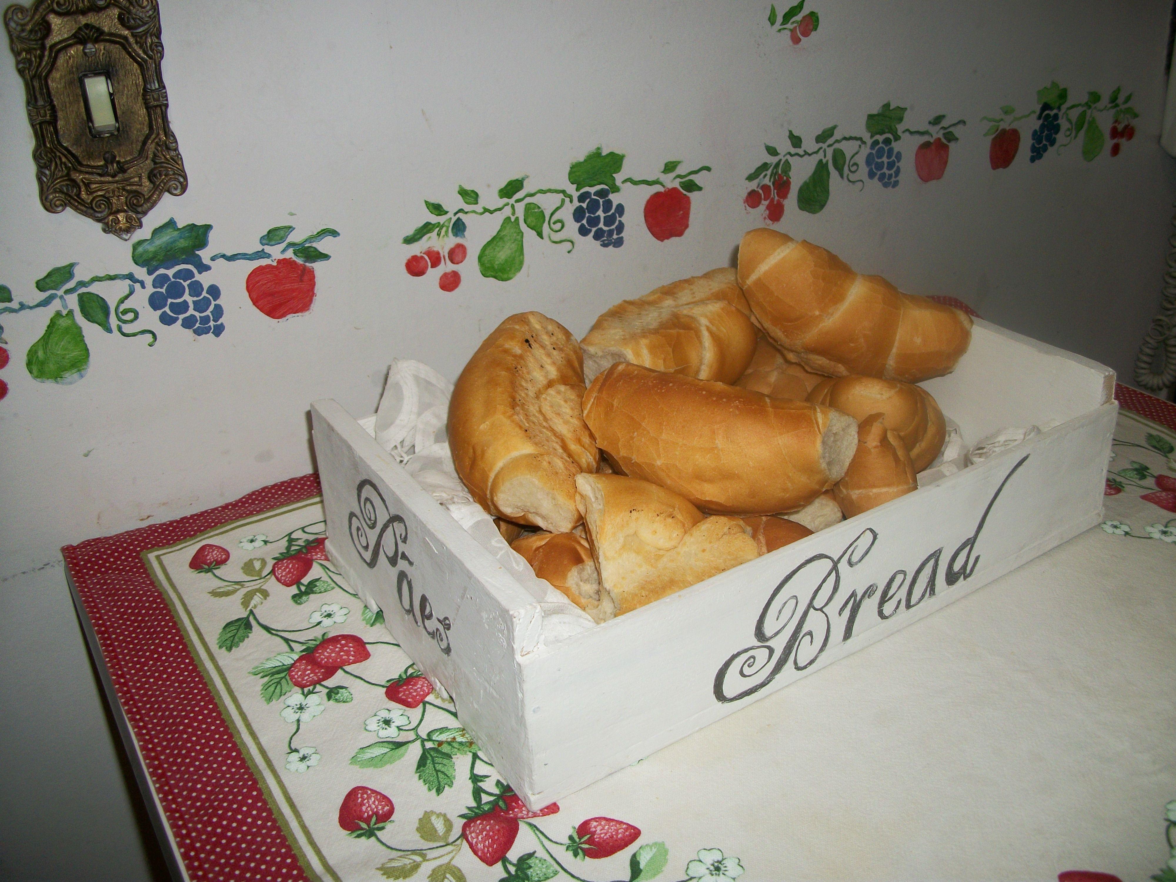 Caixote de fruta reciclado se transforma em cesto de pão. Em todos os lados escrito pão ( em inglês,português,italiano...) By Rose Oak.