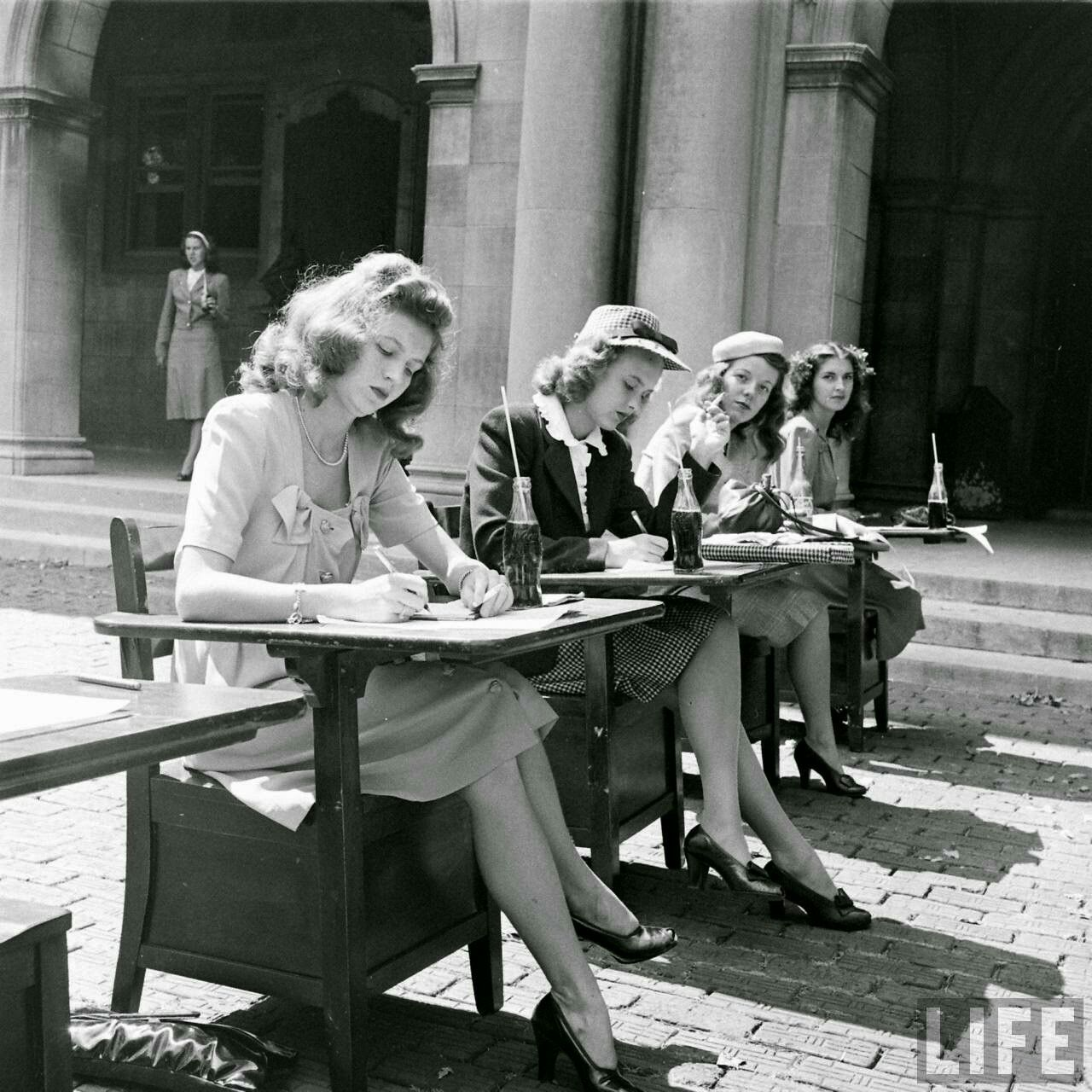 This image is so fascinating & iconic; I can't believe I've never seen it before! The outside desks, the coke bottles with straws, everyone dressed to the nines to take an exam---love it!