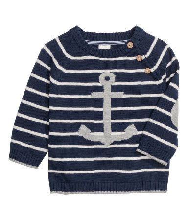 Een fijngebreide trui van katoen met raglanmouwen, een sluiting bij één van de schouders en elleboogstukken in een contrasterende kleur.