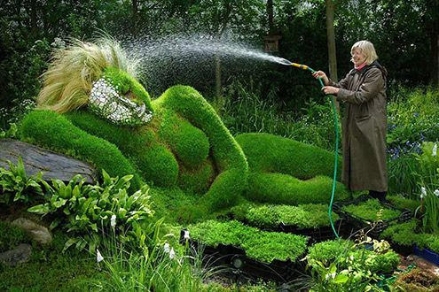 Reclining sculpture being watered, Chelsea Flower Show, UK