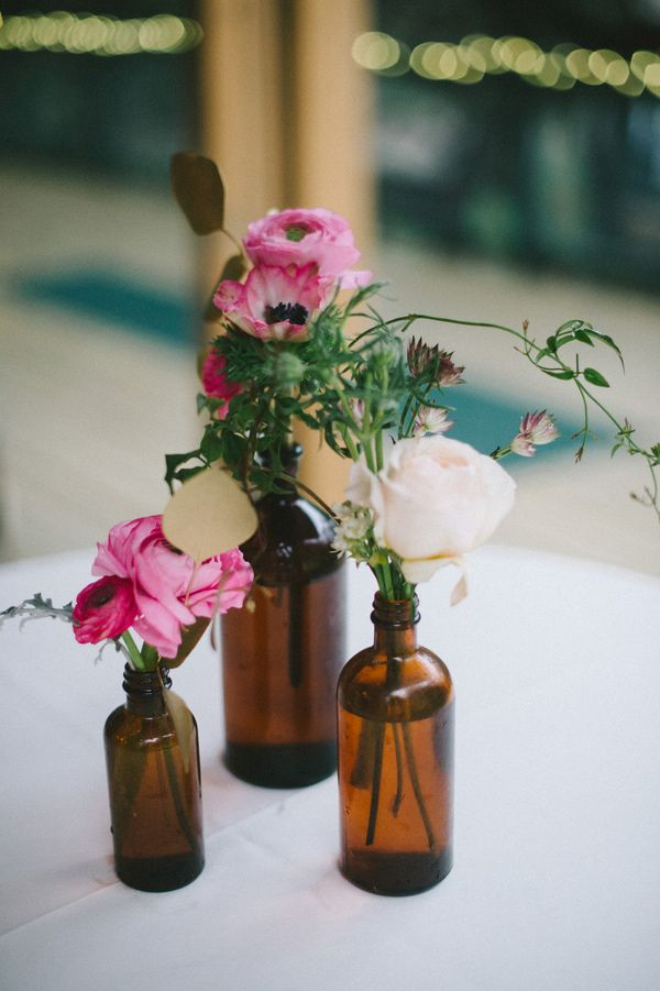 floral arrangements in amber bottles // photo by Nathan Russell // flowers by The Byrd Collective