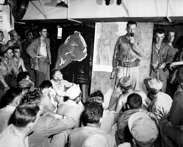 Platoon of 4th Marine Division being briefed on Iwo Jima, on a Attack Transport