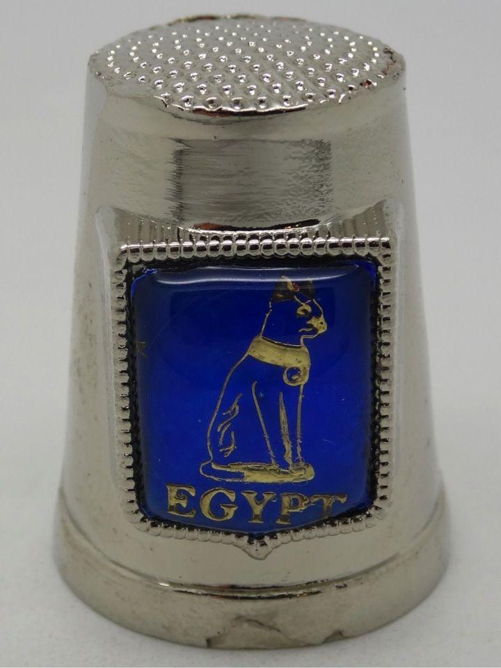 Dedal de metal con motivos egipcios de Bastet.