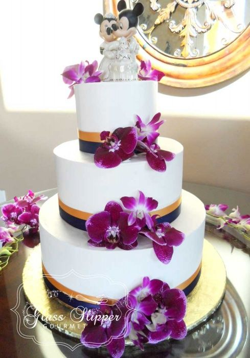 classic buttercream wedding cake with blue and gold ribbons and orchids