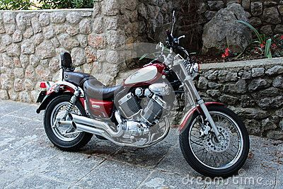 Modern new and polished red and chrome chopper parked in front of stone wall with flowers planted in the middle.