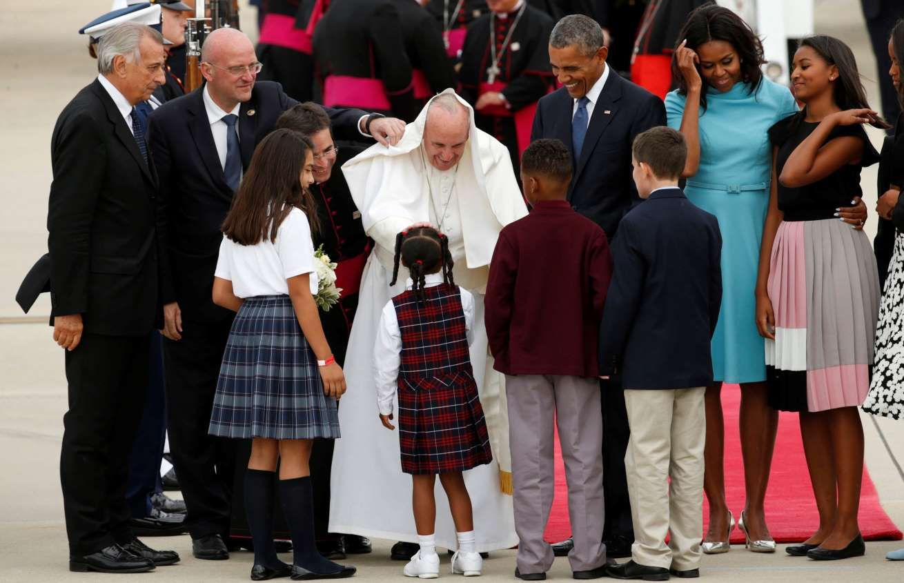 Pope Francis (C) greets children upon his arrival as he is welcomed by U.S. President Barack Obama at Joint Base Andrews outside Washington September 22, 2015.