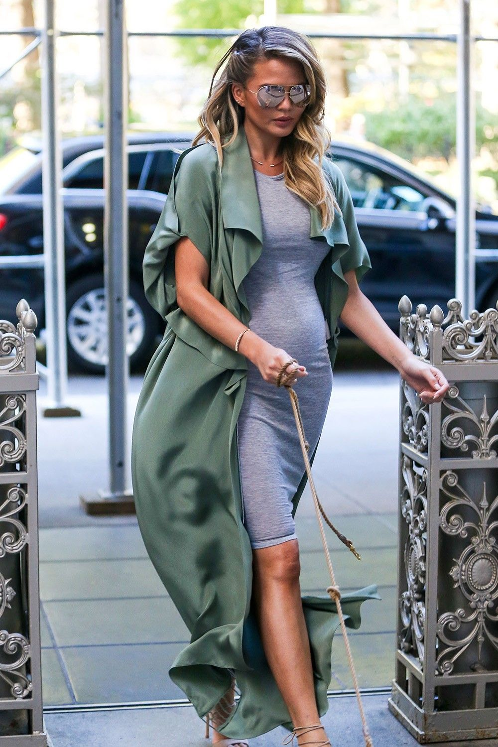 87c7f098c75 Chrissy Teigen wears grey body-con midi dress with green silk long cardigan  with nude scrappy heels and reflective aviator sunglasses