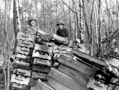 """U.S. soldiers inspect abandoned boxes of German """"Panzerfaust"""" recoiless anti-tank weapons found in the woods."""