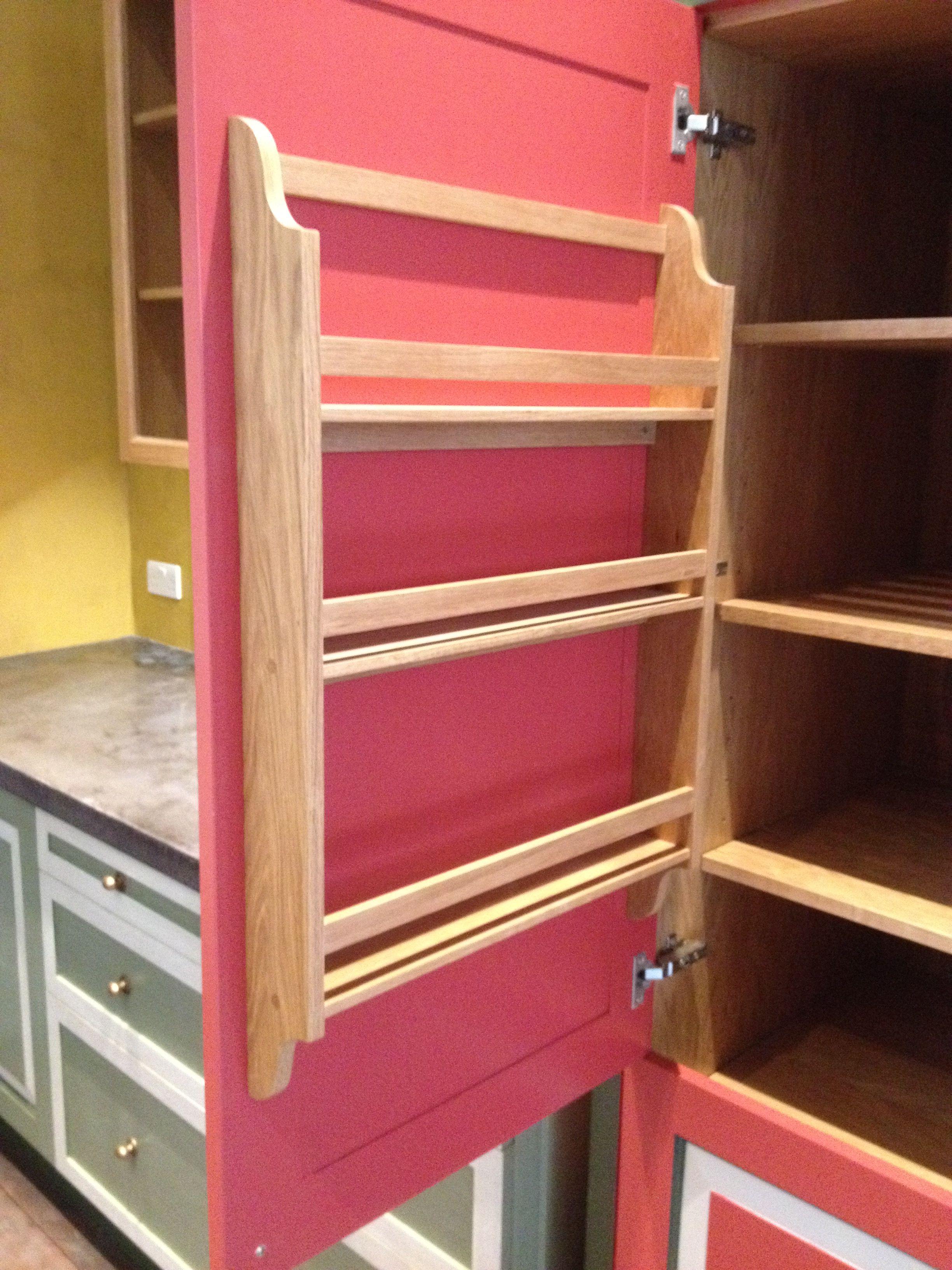small oak spice rack on the inside of the cupboard door