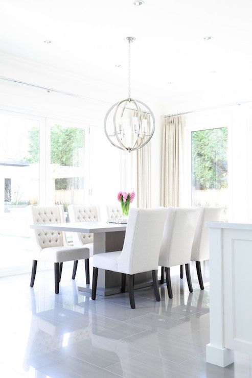 Light And Bright Dining Room Features A Gray Pedestal Dining Table Lined  With White Wingback Dining