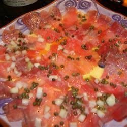 raw tuna is thinly sliced, sprinkled with onion and capers, and drizzled with lemon and olive oil for a quick and sophisticated appetizer.