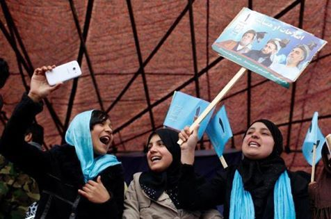 Women holding Abdullah Abdullah's portraits and protesting for, the paucity of voting papers.