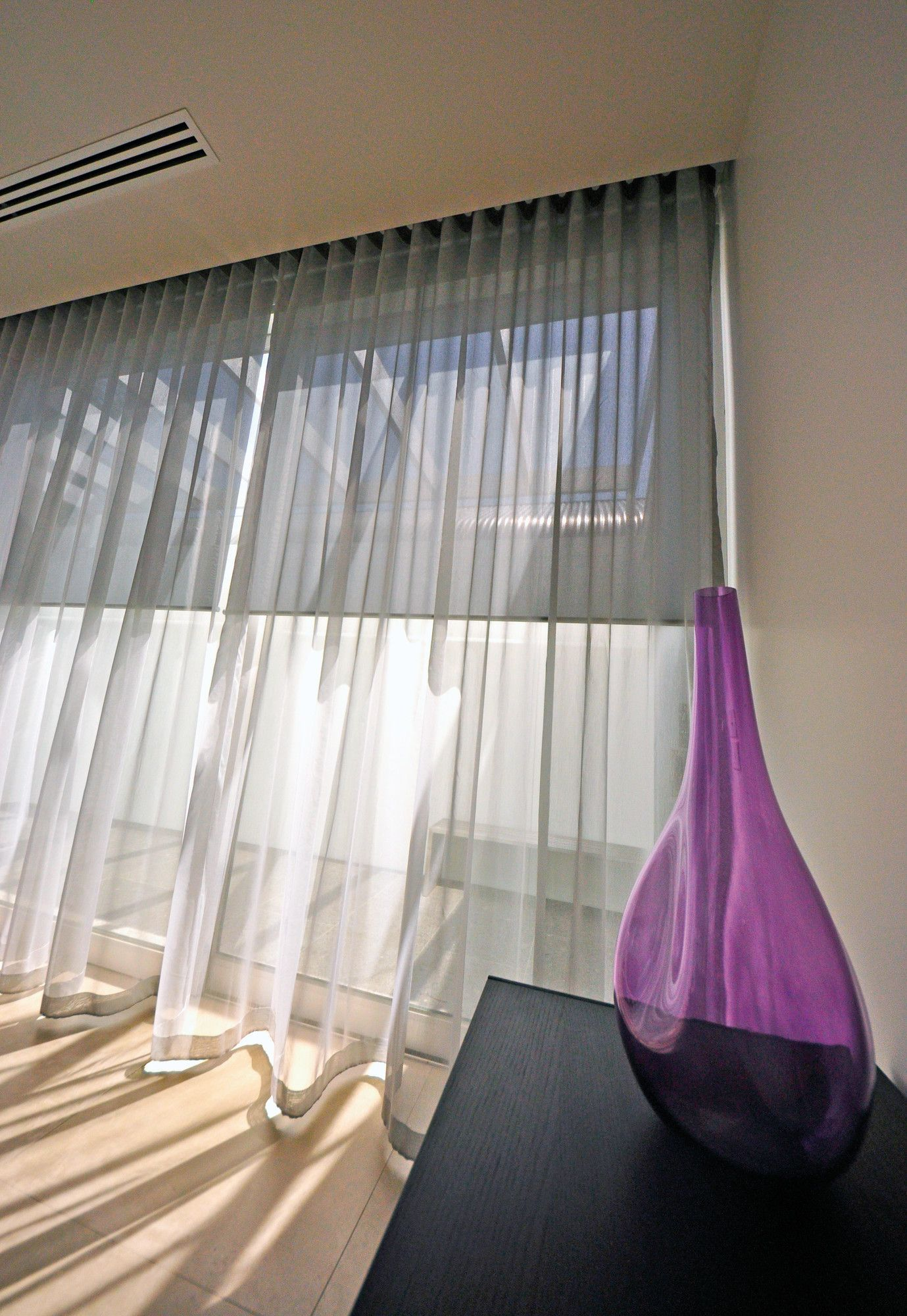 Wave curtains in the breeze with roller blinds behind picture from