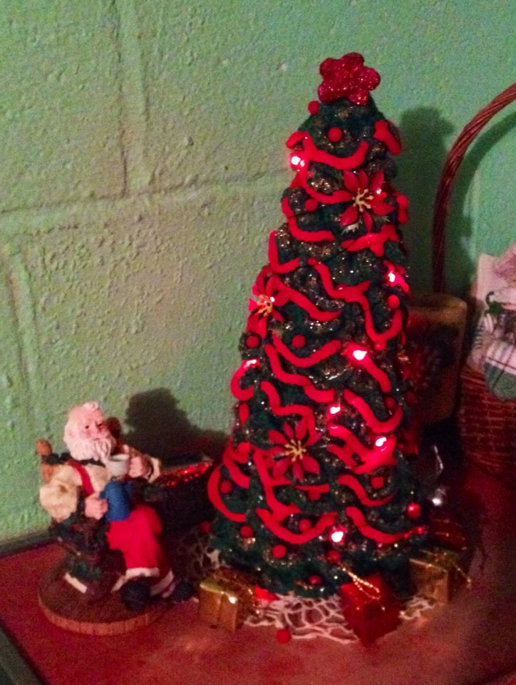christmas decorations krocheted tree cover and ornaments and battery operated lights on a styrophoam