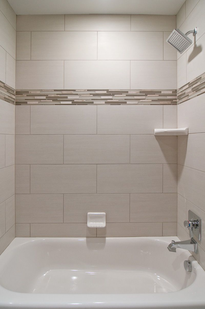 We love oversized subway tiles in this bathroom! The addition of glass accent tiles gives the space a custom look without being over the top. This is perfect for your secondary bathrooms. We also love the square showerhead from the #deltafaucet Dryden collection.