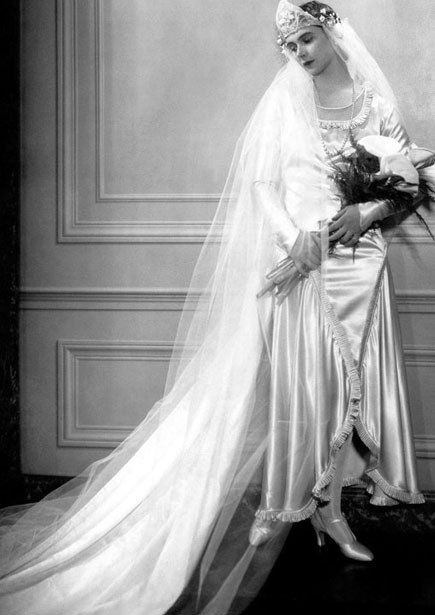 Peggy Fish in 1926. The draped silk gown daringly parts to reveal the legs (and satin slippers), and is topped with a starched Russian lace headpiece and copious tulle veil.