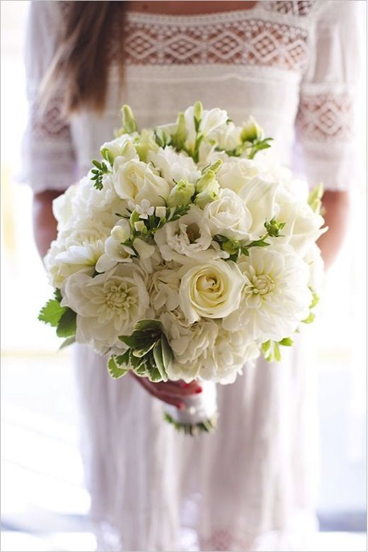 ...this one with cream hydrangeas, white ranunculus, ivory garden roses, white sweetpeas, ivory garden roses, white lisianthus, double white tulips, and variegated pittosporum wrapped in soft white ribbon with the stems showing