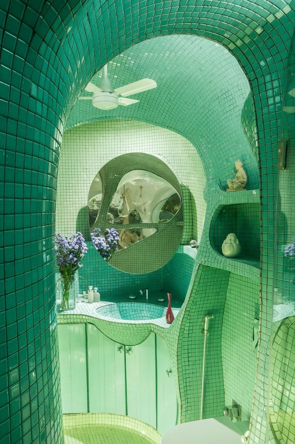 The small size of the teal mosaic tile allows it to hug the curves of the bathro…