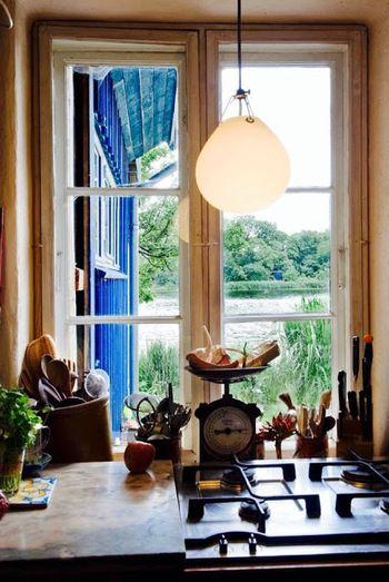 """北欧で好まれる""""温もりある光""""。  ペンダントライトは、テーブルやデスクの上部に吊るして使うのが日本では一般的ですが、北欧ではダイニングテーブルだけでなく、様々な空間でペンダントライトならではの光を上手に用いています。  ガステーブル上に吊り下げられたランプは「Louis Poulsen」の《MoserPendant》。 スウェーデンの陶芸家AnuMoserによるデザイン。  マットに仕上げられた吹きガラスのランプは、ガラスの吹き始めに生じる滴のような形。点灯していない時にも美しい空間を創造します。"""