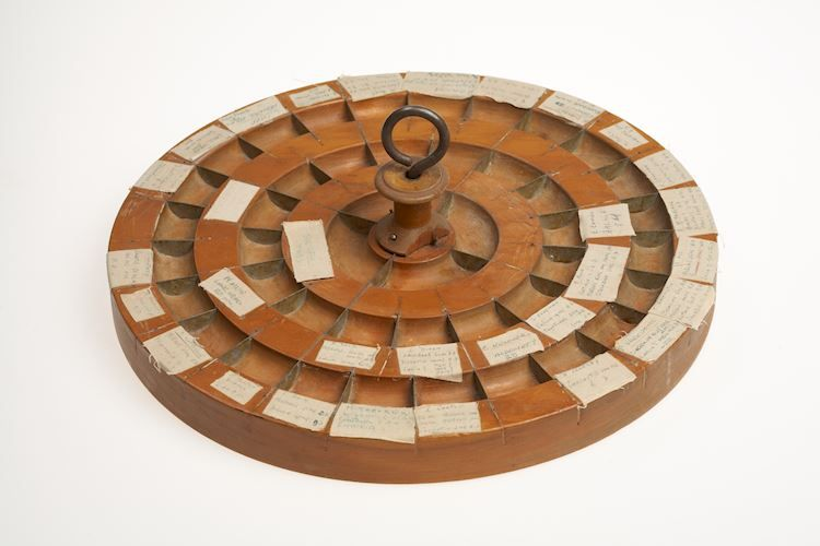 Circular wooden tray with 44 compartments.