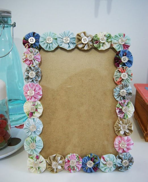 A pretty frame decorated with fabric yo-yos and buttons.