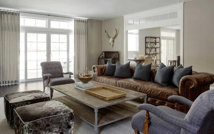 Modern Country Pillows : Modern country living room features a long brown chesterfield sofa adorned with dark grey ...