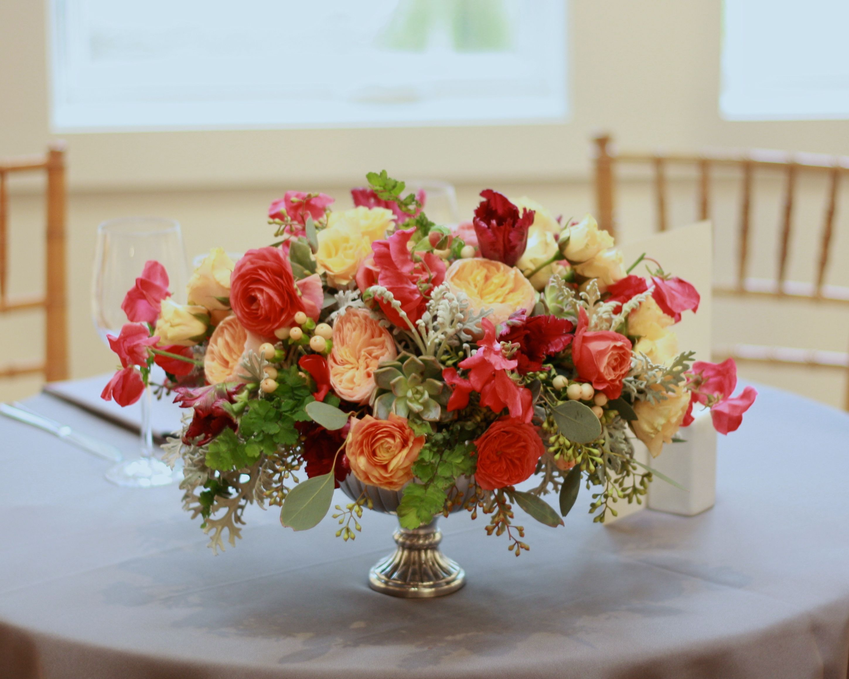 Sweetheart table arrangement featuring coral, peach and ...