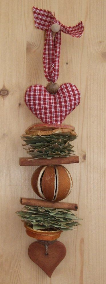 A homespun fabric heart, lavender or sandalwood ball, orange and apple slices, cinnamon sticks, bay leaves, nutmegs and a cinnamon dough heart all strung together with a homespun fabric tie at the top.