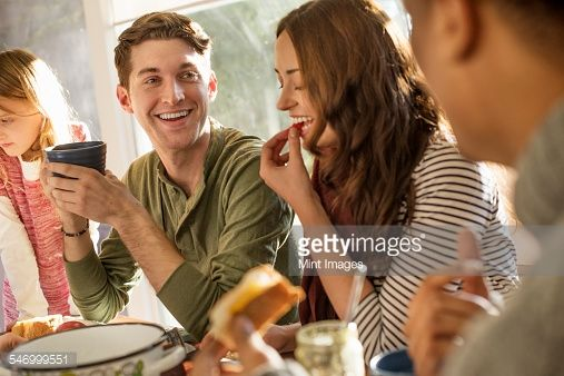 Stock-Foto : A group of people sitting at a table, smiling, eating, drinking and chatting.