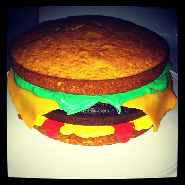 Cheeseburger cake! So easy!  Yellow cake for the buns, chocolate cake for the burger, marzipan dyed yellow and rolled out for the cheese, green frosting for the lettuce, and red and yellow frosting as ketchup and mustard!