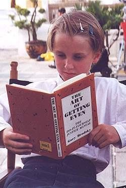 I don't know what's better: the fact that the book he's reading is called The Art of Getting Even or that he's wearing hair clips